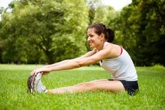 Allungando esercizio - donna di sport all'aperto Fotografia Stock