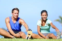 Allungando gli esercizi - coppie di forma fisica fuori Fotografia Stock Libera da Diritti