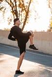 Allungando gli esercizi prima dell'addestramento corrente Immagini Stock