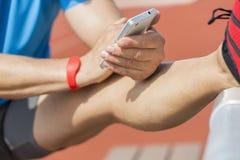 Allungando l'atleta controlla i risultati di forma fisica Fotografia Stock