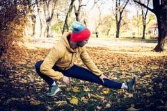 Allungando le gambe dopo il funzionamento Fondo verde degli alberi Fotografie Stock
