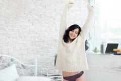 Allungandosi donna sorridente in camera da letto Fotografia Stock Libera da Diritti