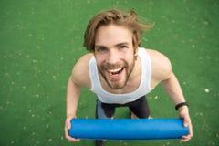 Allunghi il vostro corpo Lo sportivo porta la stuoia di yoga per la pratica all'aperto Concetto all'aperto di yoga Atleta che all Fotografie Stock