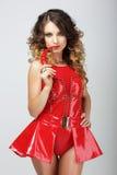 Alluring женщина в перце Chili красного резинового обмундирования сдерживая стоковое изображение rf