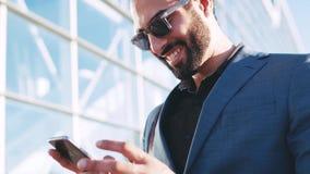 Alluring человек в модном костюме готовя вход офиса, используя его телефон, отвечая к сообщению и видеоматериал