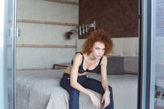 Alluring attractive young woman sitting on bed in bedroom. Alluring attractive young woman with curly red hair sitting on bed in bedroom Stock Image