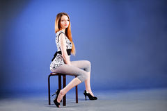 Alluring beautiful young girl on chair Royalty Free Stock Photos