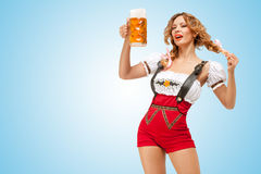 Alluring beer. Young flirting sexy Swiss woman wearing red jumper shorts with suspenders in a form of a traditional dirndl, holding a beer mug on blue Royalty Free Stock Photography