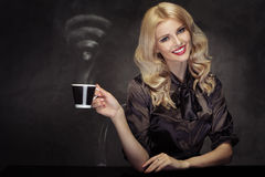Alluring blond woman drinking the coffee with the WiFi sign stea Stock Photography