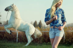 Alluring blonde beauty with majestic horse Royalty Free Stock Photos