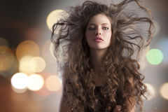 Alluring brunette and city lights. Beauty fashion portrait of a very young cute alluring brunette with long curly hair with hairstyle flying in the wind and city Stock Images