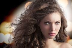 Alluring brunette with creative hairstyle. Beauty fashion portrait of a very young alluring brunette with long curly hair with hairstyle flying in the wind Stock Images