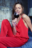 Alluring brunette drinking red wine from a glass stock photography
