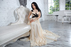 Alluring brunette relaxing on sofa in luxury interior. Royalty Free Stock Photo