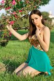 Alluring brunette sitting. On the grass and touching a branch of flowering tree Stock Photos