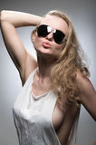 Alluring desire. Beautiful young blonde with long curly hair, standing sideways in a short white shirt and sunglasses Stock Photo