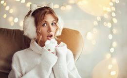 Alluring girl with cacao in garland lights. Playful pretty blonde in sweater and cute earmuffs holding cup of sweet hot drink looking sensually at camera Stock Photo