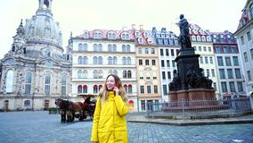 Alluring girl chatting on phone and walking in European city Dresden on background of beautiful houses and monument in. Delightful female walks around city`s stock video footage