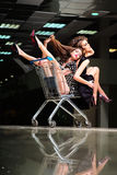 Alluring girls with shopping trolley Royalty Free Stock Photography