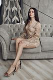 Alluring model in beige laced romper and high heels on couch.