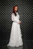 Alluring redhead lady posing in studio. On black background dressed in white long dress stock image