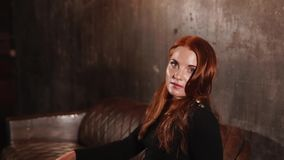 Alluring redhead woman is looking at camera and turning head to a side stock video footage