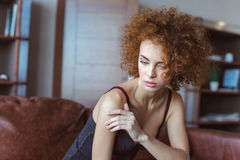 Alluring sensual  woman sitting on sofa and thinking Royalty Free Stock Images