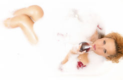 Alluring Sexy Caucasian Blond Female in Foamy Bathtub Filled with Flowery Petals Relaxing Holding a Glass of Red Wine Stock Photography