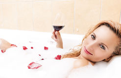 Alluring Sexy and Sensual Blond Female Relaxing in Foamy Bath Covered with Rose Petals.Drinking Red Wine Stock Photo