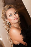 Blonde sexy woman In evening dress in luxury interior. Stylish rich slim girl with hairstyle and bright makeup in apartment. Royalty Free Stock Photos