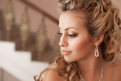 Blonde woman with diamond jewelry with hairstyle and makeup Royalty Free Stock Image