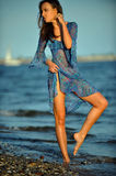 Alluring woman posing on the beach in floral transparent dress. Stock Photos