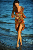 Alluring woman posing on the beach in floral transparent dress. Stock Images