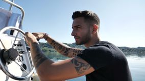 Alluring tattooed man in boat. Portrait of young bearded handsome man with tattooed body looking at camera sailing in boat stock video