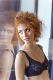 Alluring tender woman in lace bra standing at the window Stock Photography