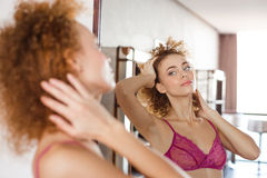 Alluring tender woman  standing in front of the mirror Stock Image