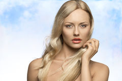 Alluring woman with flying hair. Close-up portrait of alluring blonde woman with naked shoulders, pure skin and flying silky hair royalty free stock photo