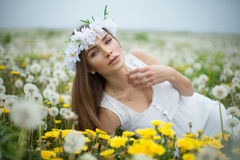 Alluring woman lying on a meadow. Full of dandelions Royalty Free Stock Images