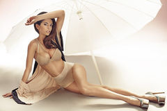 Alluring woman lying under the white umbrella Stock Photography