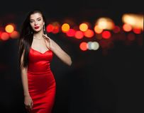 Alluring woman in red silky dress and black carnival mask on background with abstract night glitter bokeh.  stock photo