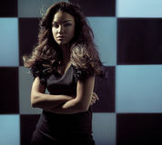 Alluring woman standing over the chessboard background Royalty Free Stock Images