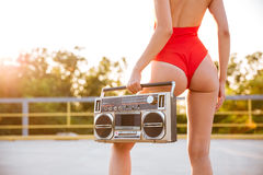 Alluring woman in swimsuit standing outdoors and holding old boombox. Back view of alluring young woman in red swimsuit standing outdoors and holding old boombox royalty free stock images