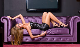 Woman wearing a short dress relaxing on a sofa Royalty Free Stock Photos