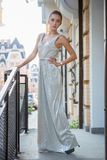 Alluring young woman. Posing on the street near the handrail dressed in a long dress stock photos