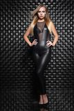 Alluring young woman posing in the studio. Dressed in a black leather suit stock photos