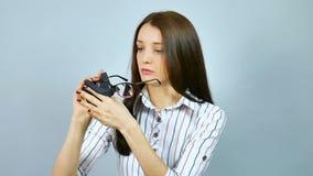 Allvarlig affärskvinna i den vita skjortan med röda och blåa band som torkar hennes optiska glasögon och After det bära lager videofilmer
