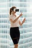 Allvarlig affärskvinna i försökande virtuell verklighet 3d för VR-hörlurar med mikrofon till Royaltyfri Foto