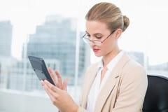 Allvarlig affärskvinna med exponeringsglas genom att använda räknemaskinen fotografering för bildbyråer