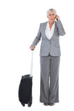 Allvarlig affärskvinna med hennes bagage och att kalla någon Royaltyfri Fotografi