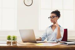 Allvarlig affärskvinna som arbetar på bärbara datorn på kontoret Royaltyfri Bild